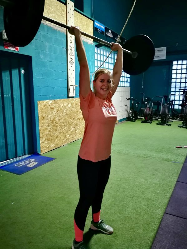 woman lifting olympic weightlifting bar in crossfit gym